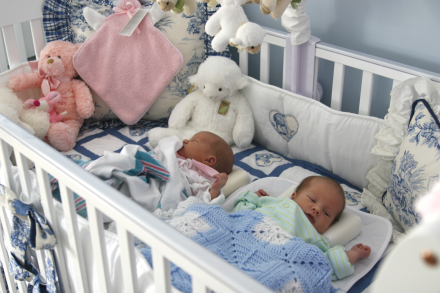 twins sleep together in same crib