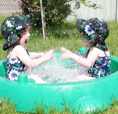 Two-year-old Twins splashing each other in the pool.